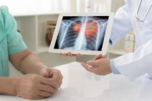 Doctor explaining results of lung check up from x-ray scan chest on digital tablet screen to patient.