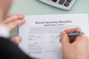 Man filling up social security benefits form.