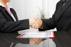 A Richmond motorcycle accident attorney shaking hands with a client.