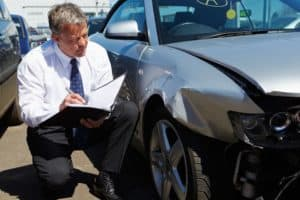 adjuster inspects car involved in accident